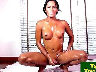 Oiled ladyboy stripteases before masturbating