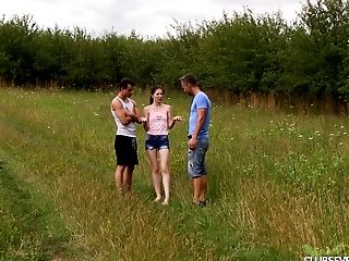 Skinny teen in a grassy field fucking two horny guys